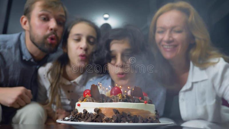Gelukkige het glimlachen jongens blazende kaarsen op haar verjaardagscake kinderen die door hun familie worden omringd De cake va royalty-vrije stock afbeeldingen