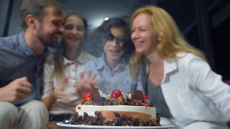 Gelukkige het glimlachen jongens blazende kaarsen op haar verjaardagscake kinderen die door hun familie worden omringd De cake va stock foto