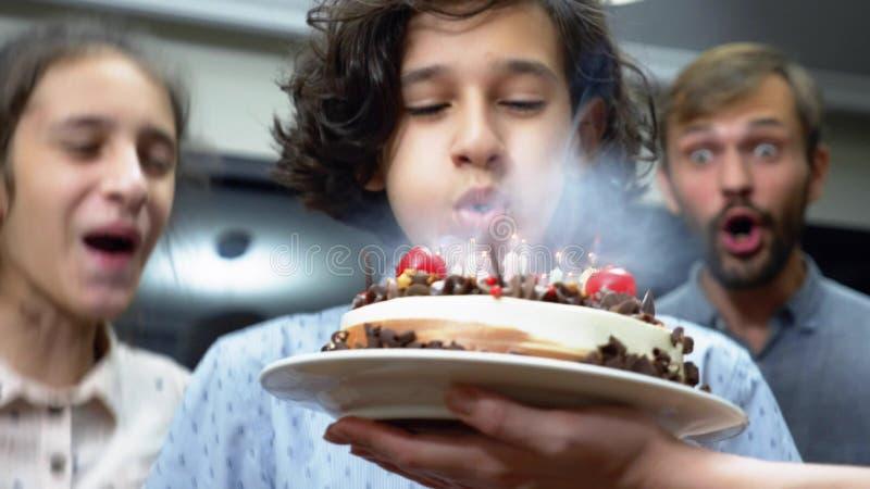 Gelukkige het glimlachen jongens blazende kaarsen op haar verjaardagscake kinderen die door hun familie worden omringd De cake va stock afbeelding