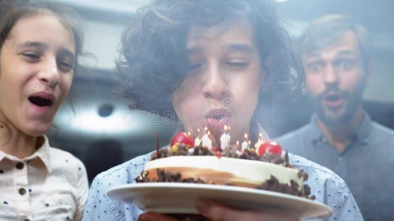 Gelukkige het glimlachen jongens blazende kaarsen op haar verjaardagscake kinderen die door hun familie worden omringd De cake va royalty-vrije stock foto