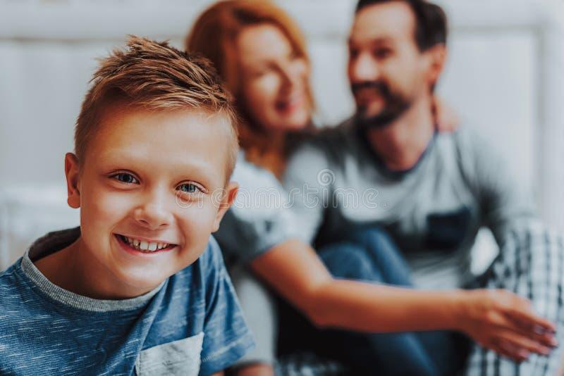 Gelukkige het glimlachen jongenszitting met ouders op bed stock foto
