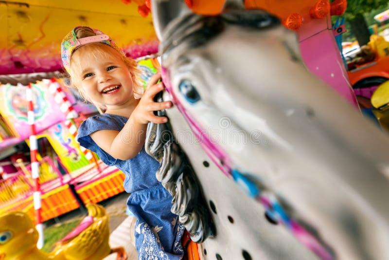 gelukkige het glimlachen kindzitting op paardcarrousel bij pretpark royalty-vrije stock fotografie