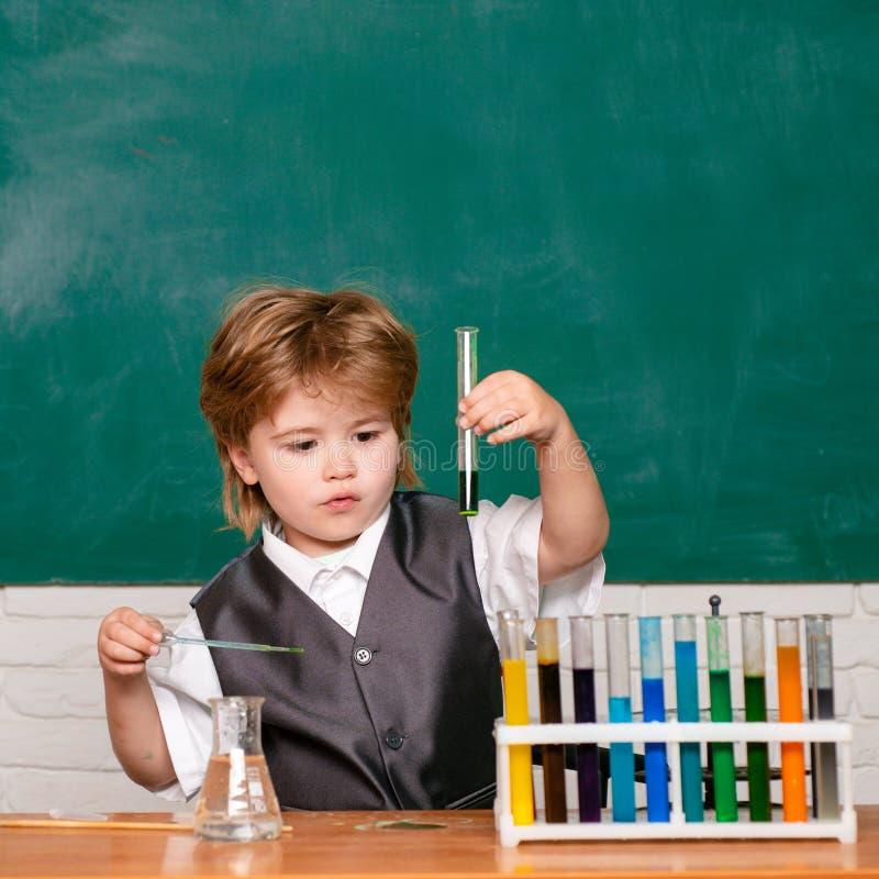 Gelukkige het glimlachen leerlingstekening bij het bureau schoolkind De lessen van de schoolchemie Ondergeschikte jaarchemie Bord royalty-vrije stock fotografie