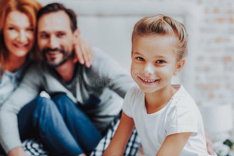Gelukkige het glimlachen meisjeszitting met ouders op bed stock afbeelding