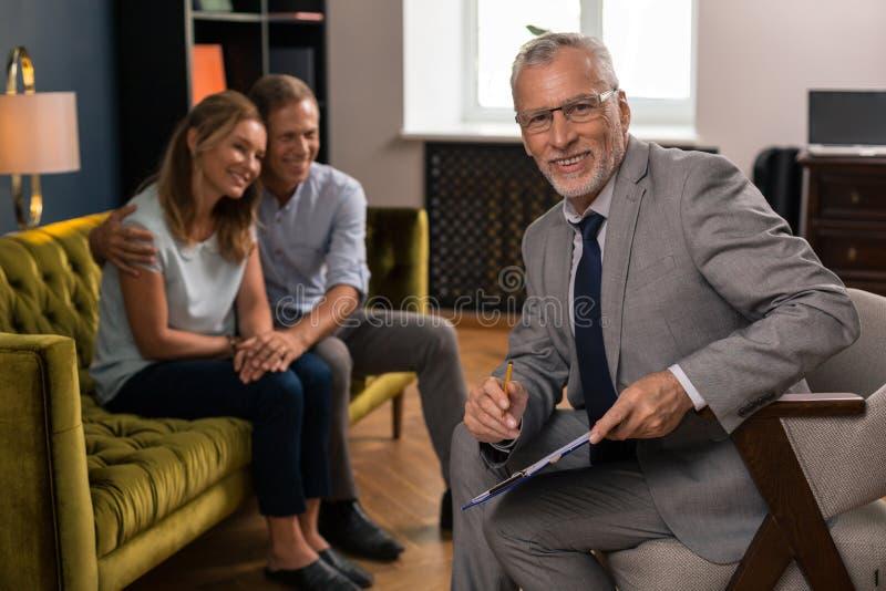 Gelukkige het glimlachen psycholoogzitting naast zijn patiënten royalty-vrije stock afbeeldingen