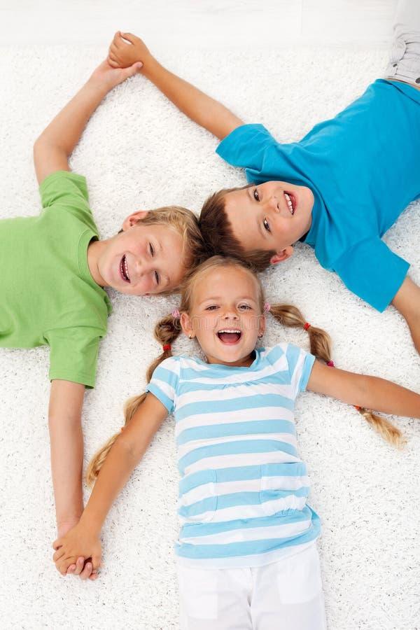 Gelukkige het lachen jonge geitjes op de vloer stock foto's
