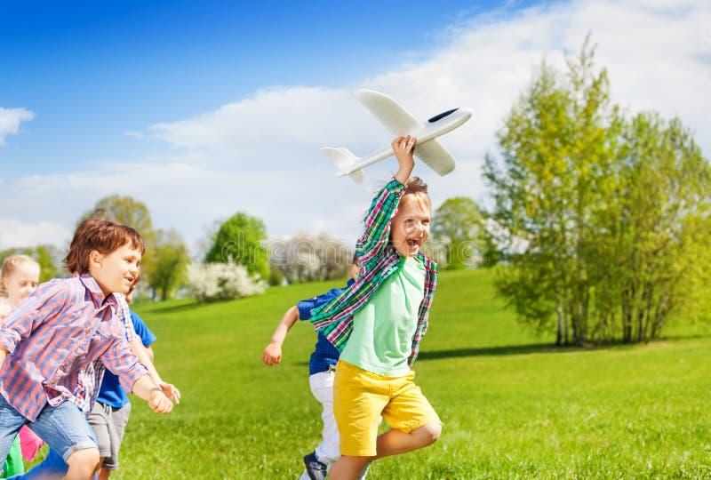 Gelukkige het lopen jonge geitjes met wit vliegtuigstuk speelgoed stock afbeeldingen
