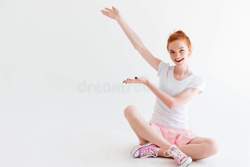 Gelukkige het meisjeszitting van de gembervrouw op vloer en het tonen van iets stock afbeelding