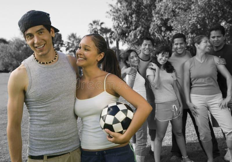 Gelukkige het voetbalbal die van de paarholding met vrienden bij park genieten van royalty-vrije stock foto's