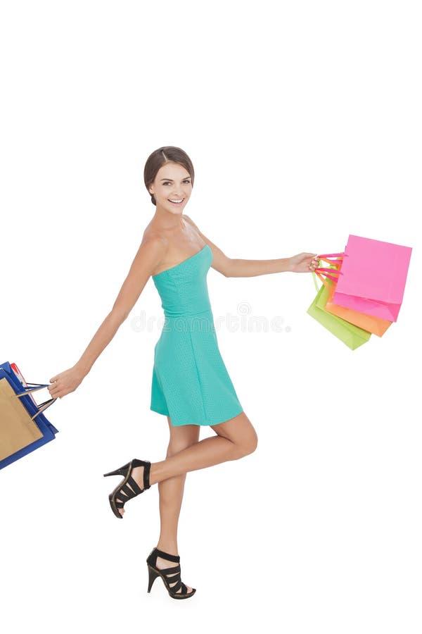 Gelukkige het winkelen vrouw slingerende het winkelen zak terwijl het lopen royalty-vrije stock foto
