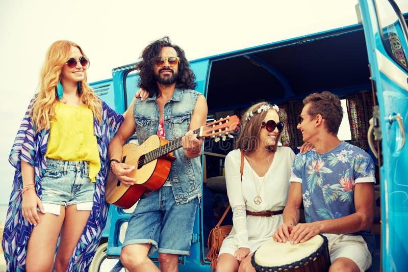 Gelukkige hippievrienden die muziek over minivan spelen royalty-vrije stock foto