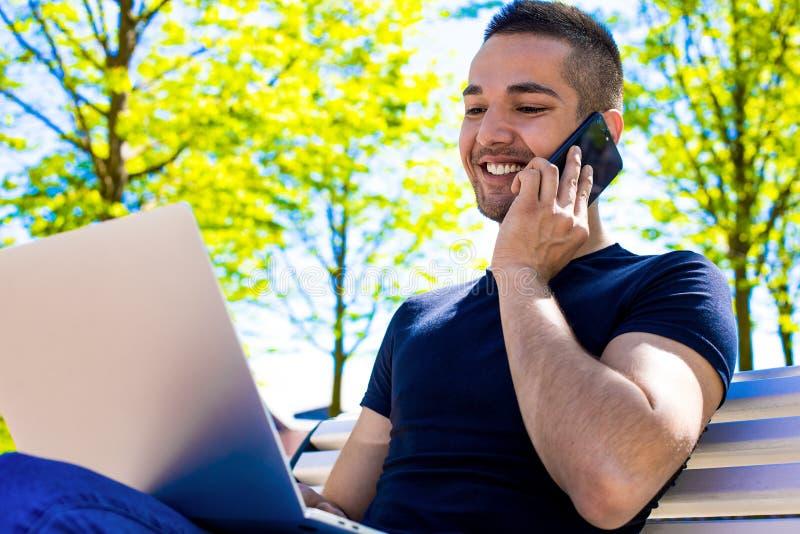 Gelukkige hipsterkerel die via mobiele telefoon spreken en toepassingen op notitieboekje gebruiken royalty-vrije stock foto's