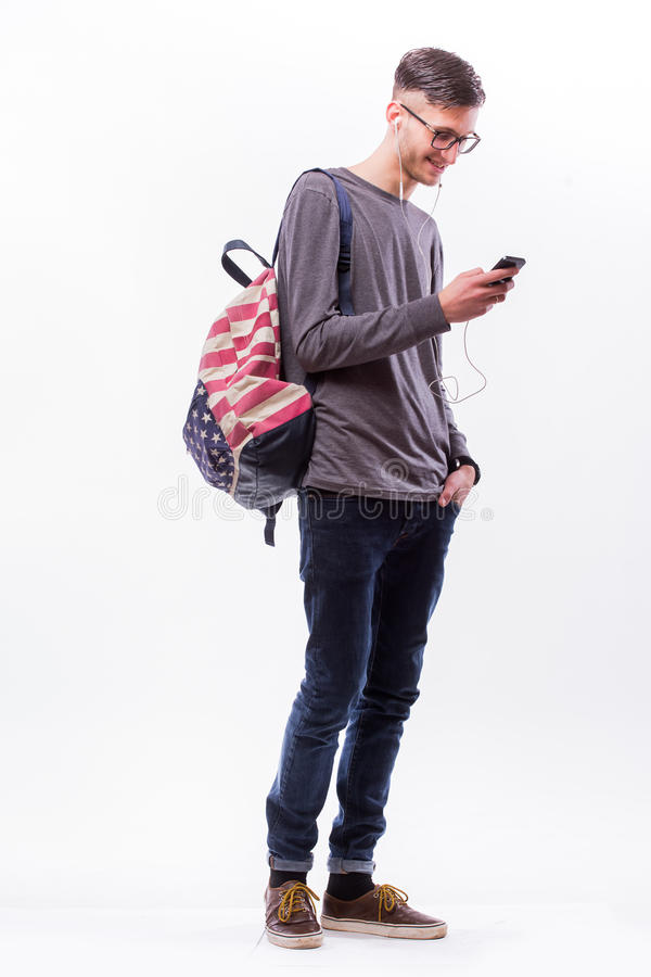 Gelukkige hipsterkerel in glazen met rugzak die een slimme telefoon met behulp van om te luisteren muziek met hoofdtelefoons royalty-vrije stock afbeelding