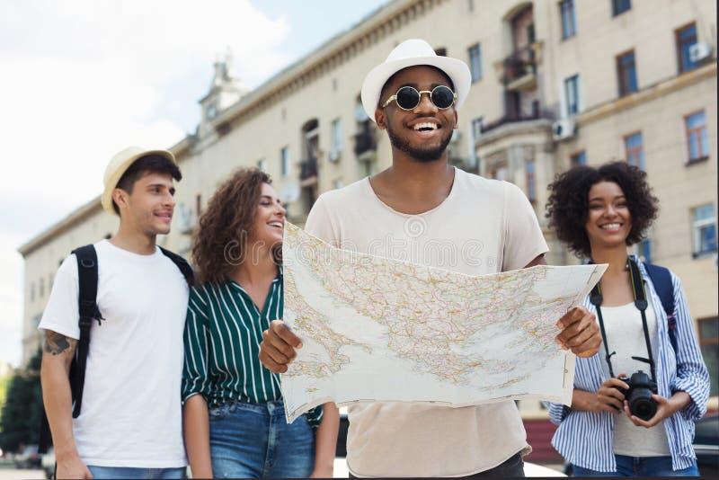 Gelukkige hipsters gebruikend navigatiekaart om de stad te onderzoeken stock foto