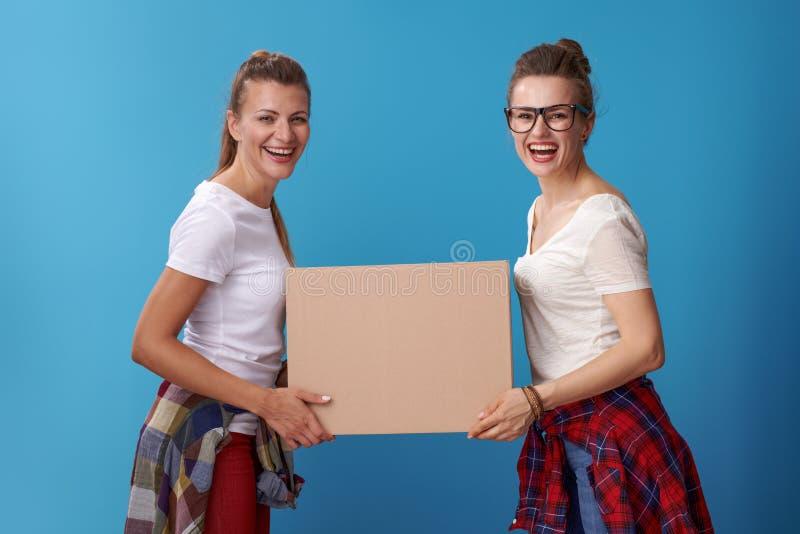 Gelukkige hipstervrienden die kartondoos samen op blauw houden royalty-vrije stock afbeelding