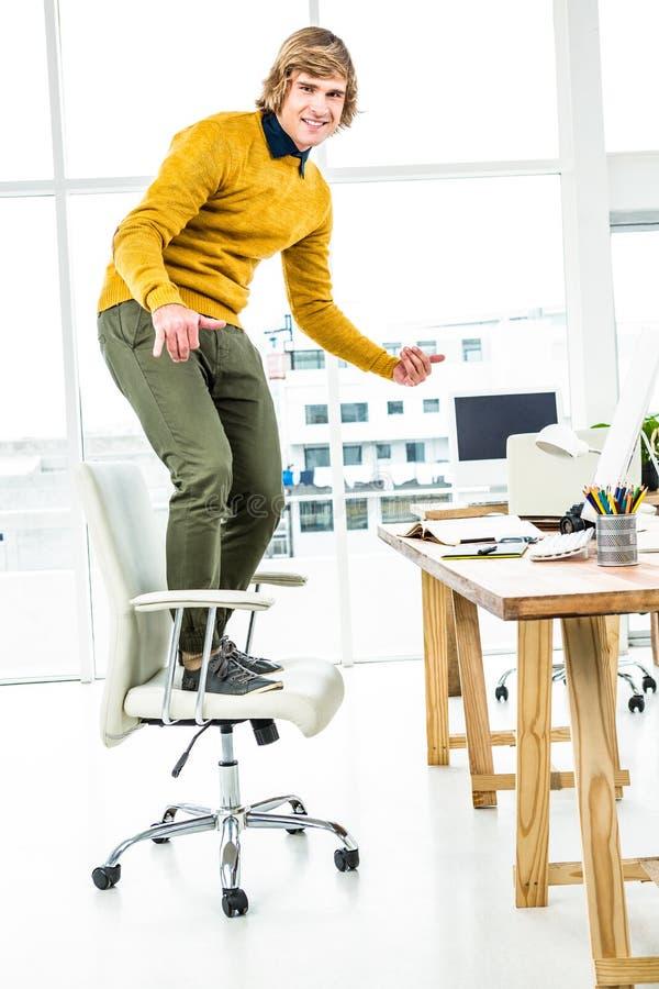Gelukkige hipsterzakenman die zich op zijn stoel bevinden stock foto
