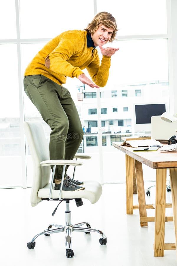 Gelukkige hipsterzakenman die zich op zijn stoel bevinden royalty-vrije stock foto