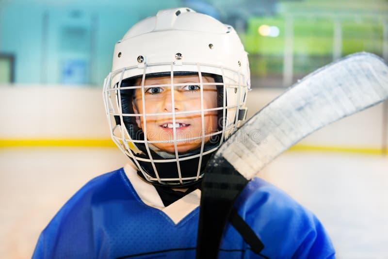 Gelukkige hockeyspeler die op het ijs voorbereidingen treffen uit te gaan stock afbeelding