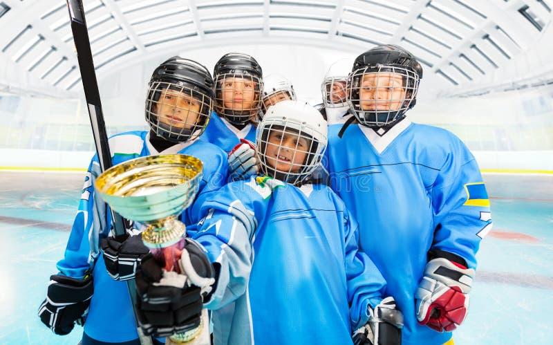 Gelukkige hockeyspelers met trofee op ijsbaan stock afbeeldingen