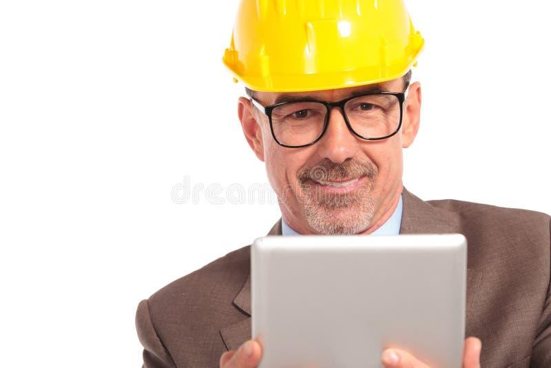 Gelukkige hogere architectenlezing op zijn tabletstootkussen stock afbeelding