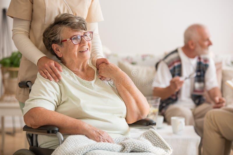 Gelukkige hogere damezitting bij rolstoel in verpleeghuis voor bejaarden stock afbeeldingen