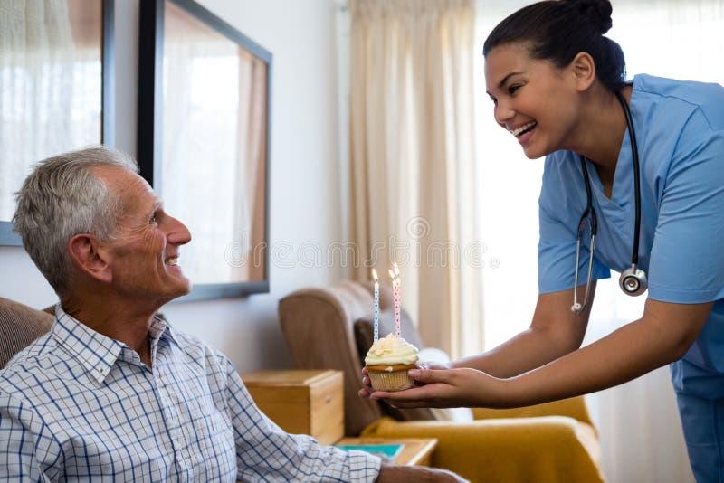 Gelukkige hogere mens die de kopcake van de artsenholding bekijken met kaars in verpleeghuis stock afbeeldingen