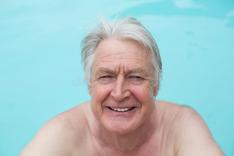 Gelukkige hogere mens die in pool zwemmen stock afbeelding