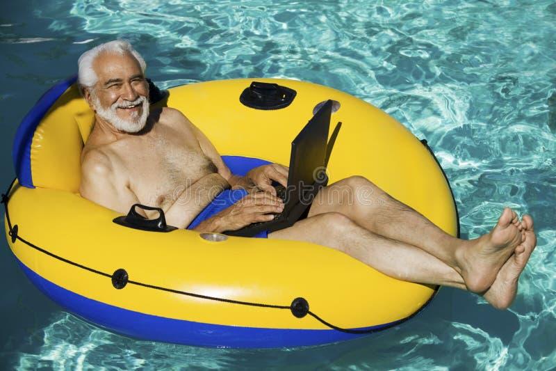 Gelukkige Hogere Mens met Laptop op Opblaasbaar Vlot in Pool stock foto's