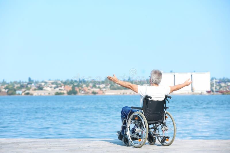 Gelukkige hogere mens in rolstoel dichtbij rivier stock afbeelding