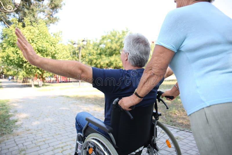 Gelukkige hogere mens in rolstoel en zijn vrouw in openlucht royalty-vrije stock foto