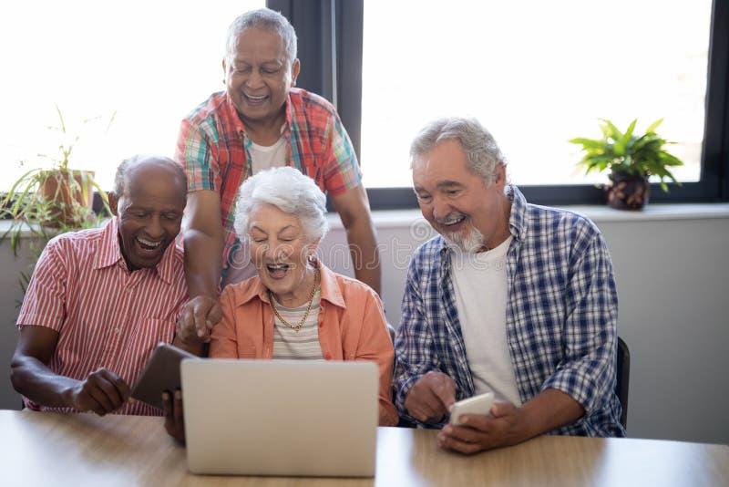 Gelukkige hogere mensen die technologie gebruiken bij verpleeghuis stock afbeelding