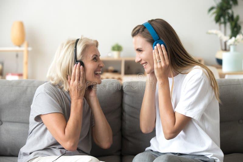 Gelukkige hogere moeder en volwassen dochter het luisteren muziek in headph stock afbeelding