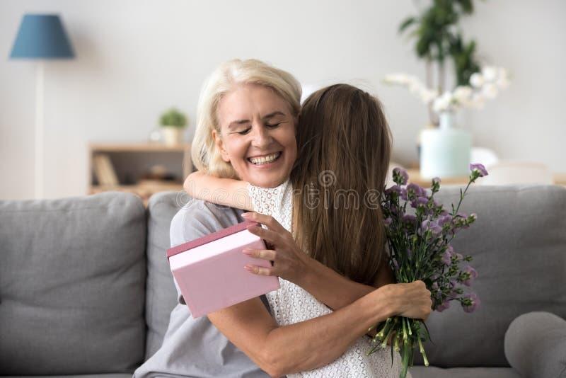 Gelukkige hogere oma die kleindochter koesteren die voor gift danken en stock foto