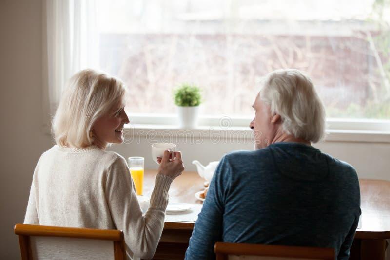 Gelukkige hogere paar het drinken thee die, achtermening thuis babbelen stock afbeelding