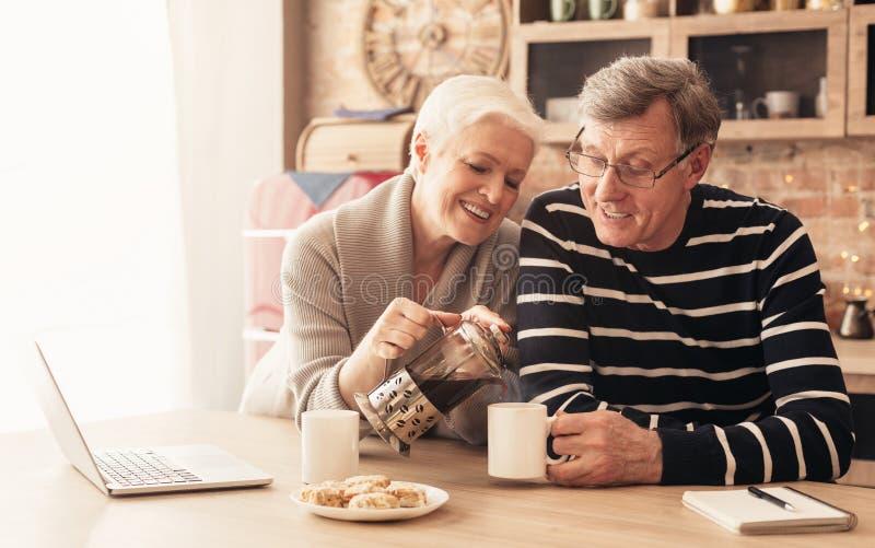 Gelukkige hogere paar het drinken thee in keuken stock afbeeldingen