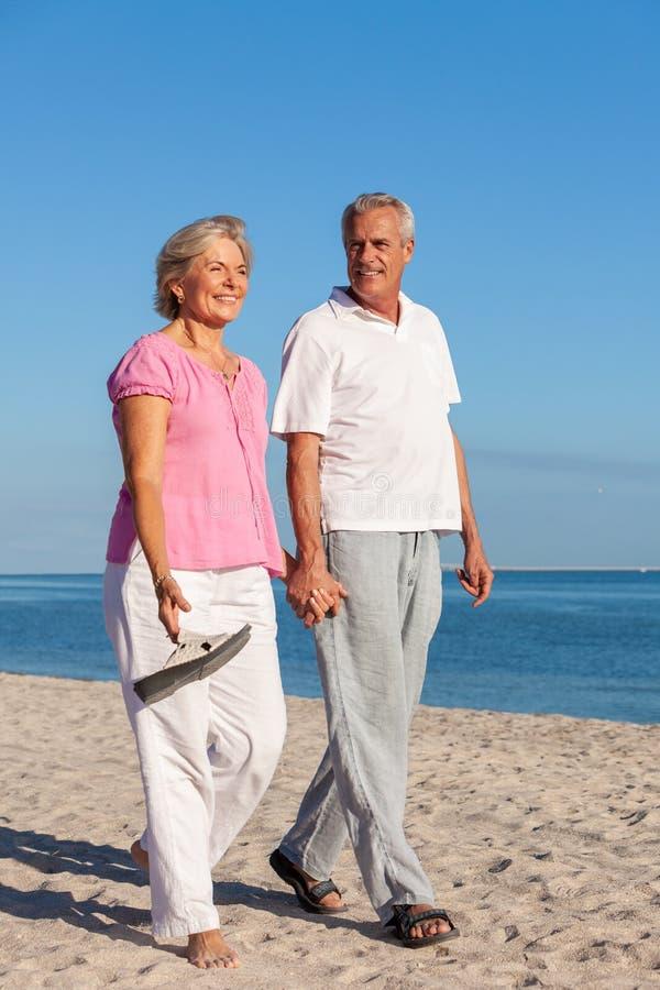 Gelukkige Hogere Paar het Lopen Holdingshanden op een Strand royalty-vrije stock fotografie
