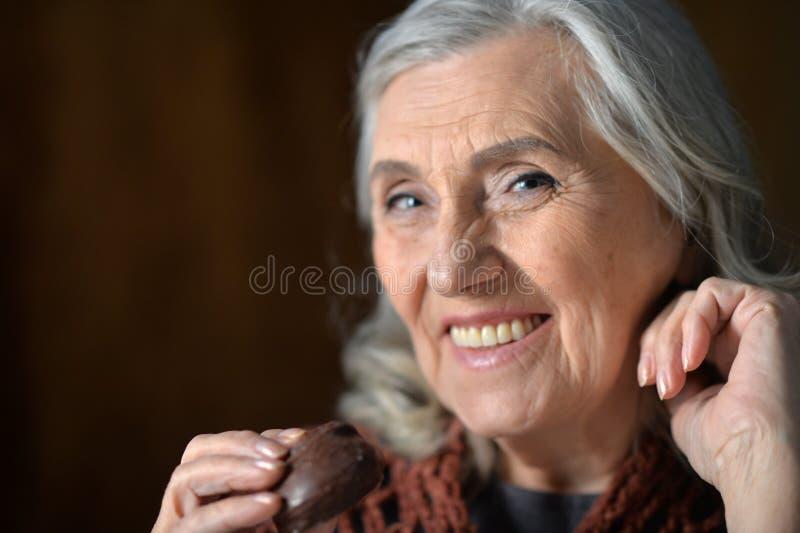 Gelukkige hogere vrouw die chocoladekoekje thuis eten royalty-vrije stock foto