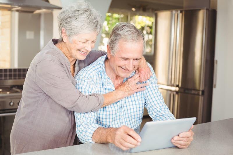 Gelukkige hogere vrouw die de mens omhelzen die tablet gebruiken stock foto's