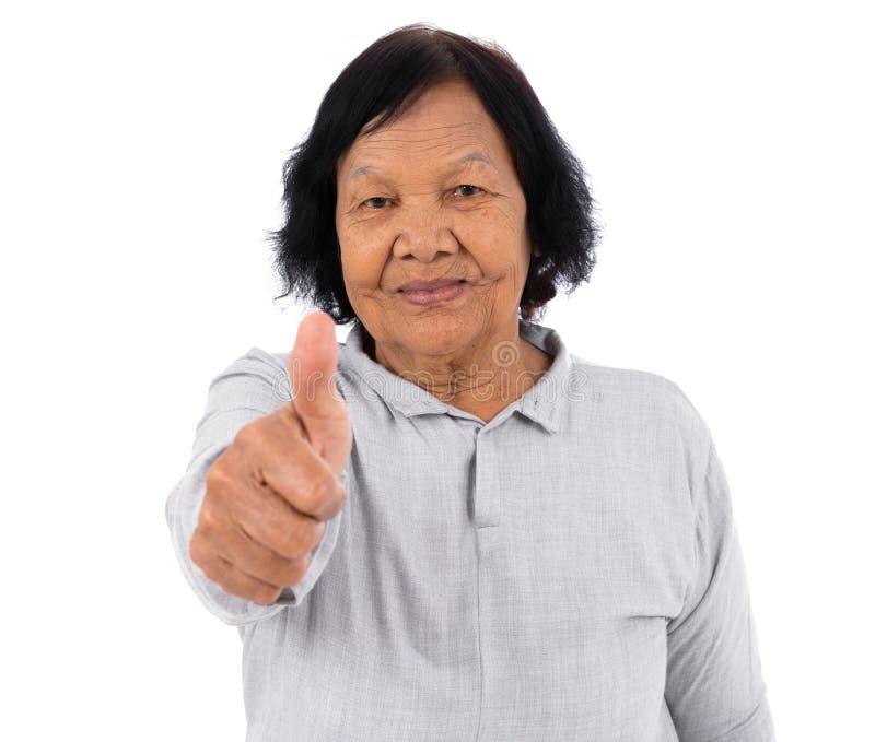Gelukkige hogere vrouw die die duimen tonen omhoog op witte backgroun worden geïsoleerd royalty-vrije stock foto's