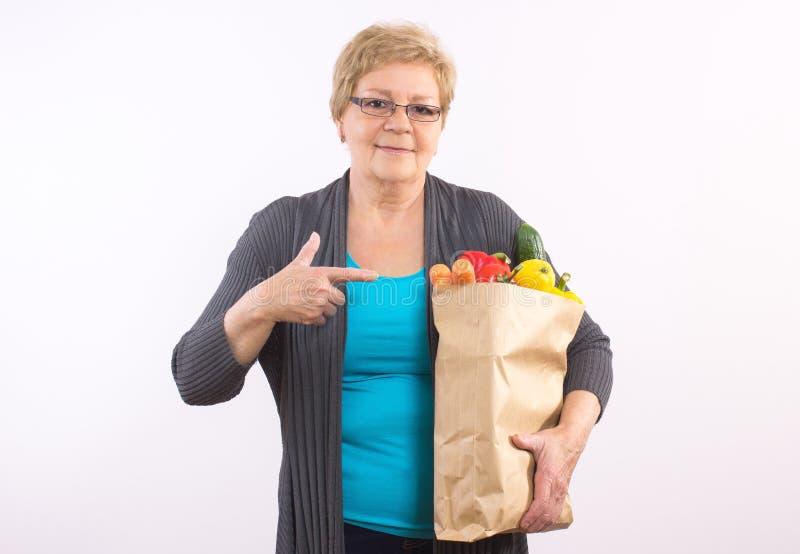 Gelukkige hogere vrouw die het winkelen zak met vruchten en groenten, gezonde voeding in oude dag tonen stock foto
