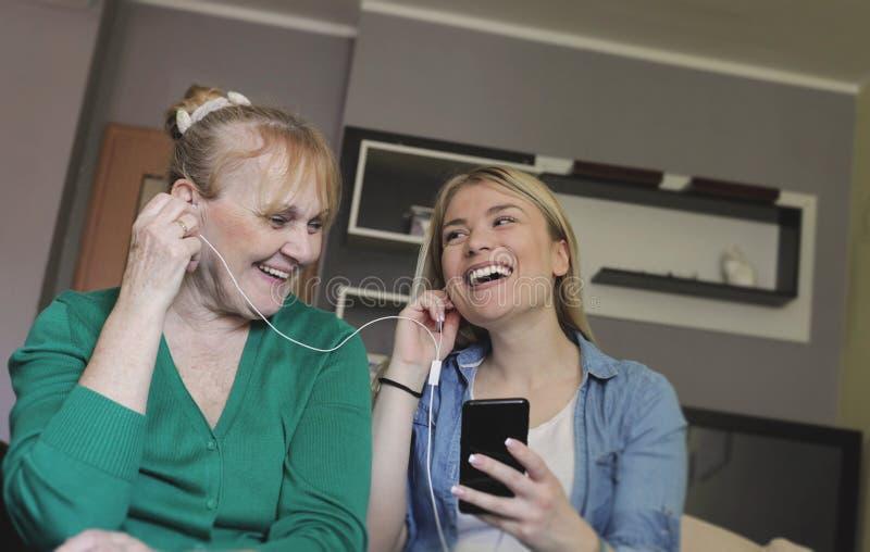 Gelukkige hogere vrouw en haar dochter die aan muziek samen luisteren royalty-vrije stock foto's