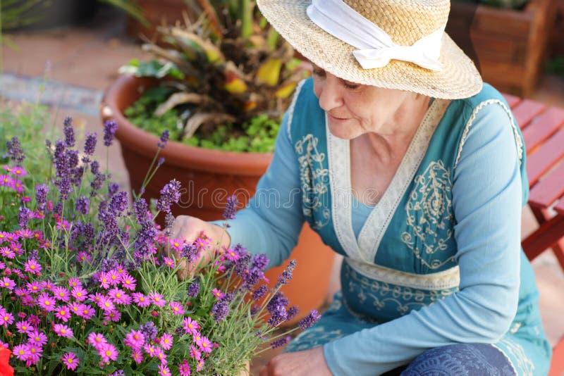 Gelukkige hogere vrouw met bloemen royalty-vrije stock foto's