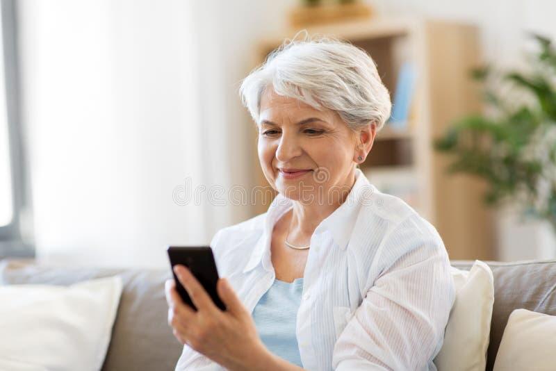 Gelukkige hogere vrouw met smartphone thuis royalty-vrije stock foto