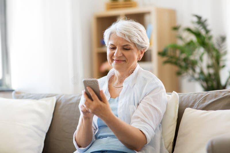 Gelukkige hogere vrouw met smartphone thuis stock fotografie