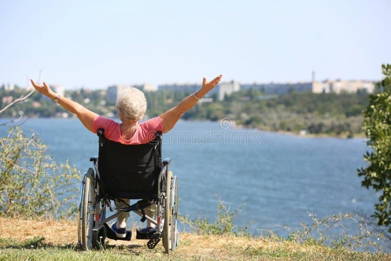 Gelukkige hogere vrouw in rolstoel dichtbij rivier royalty-vrije stock afbeelding