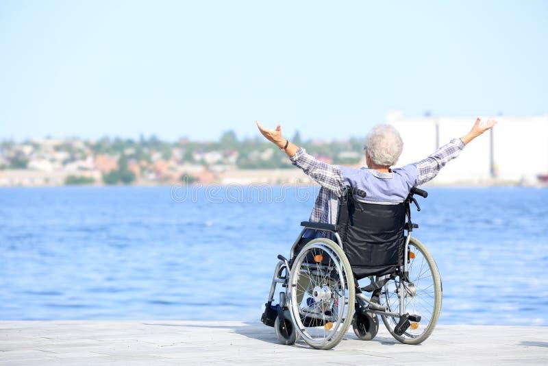 Gelukkige hogere vrouw in rolstoel dichtbij rivier stock afbeeldingen