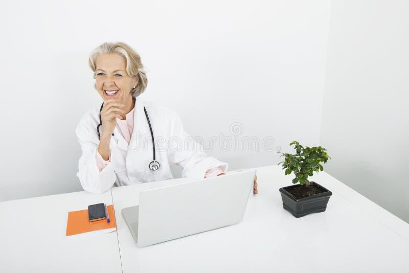 Gelukkige hogere vrouwelijke arts met laptop bij bureau in kliniek royalty-vrije stock afbeeldingen