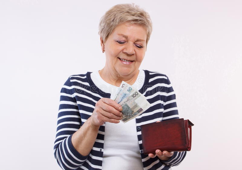 Gelukkige hogere vrouwelijke holdingsportefeuille met het geld van de poetsmiddelmunt, concept financiële zekerheid in oude dag royalty-vrije stock foto