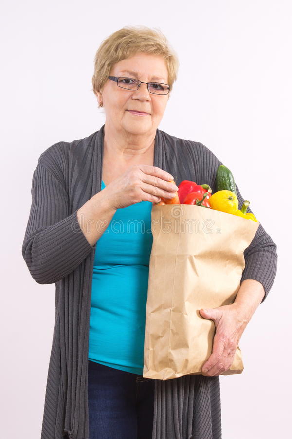 Gelukkige hogere vrouwenholding het winkelen zak met vruchten en groenten, gezonde voeding in oude dag royalty-vrije stock afbeeldingen
