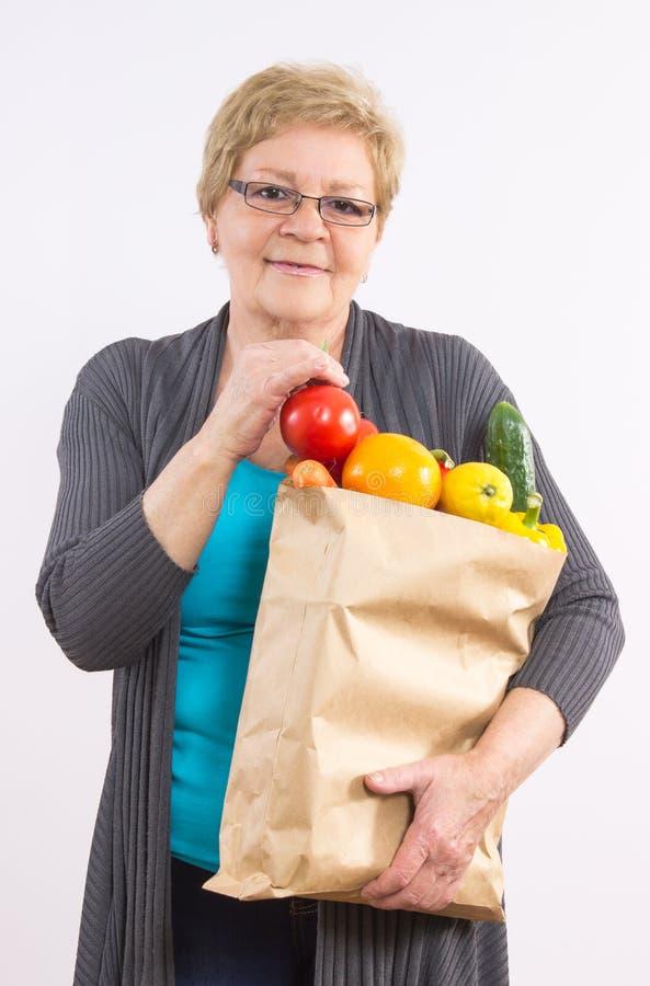 Gelukkige hogere vrouwenholding het winkelen zak met vruchten en groenten, gezonde voeding in oude dag royalty-vrije stock fotografie